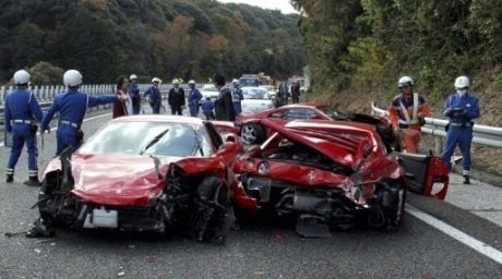 Police officers inspecting damaged Ferrari sports cars on the Chugoku highway in Shimonoseki, Yamaguchi prefecture, western Japan following a 14-vehicle pile up. ©AFP