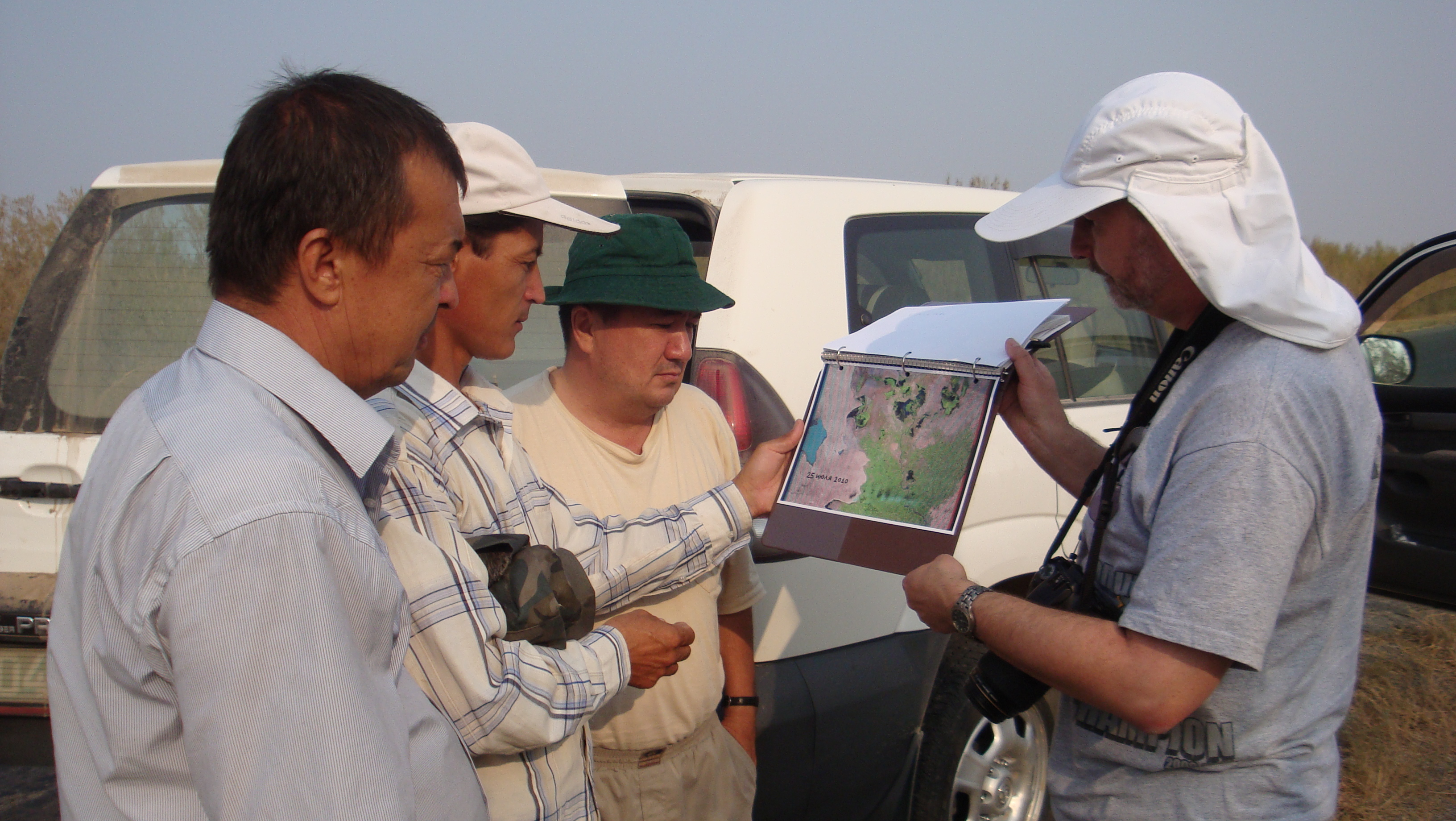 Alex Latchininsky wears a protective hat while do field work with Uzbek locust experts near the Aral Sea.