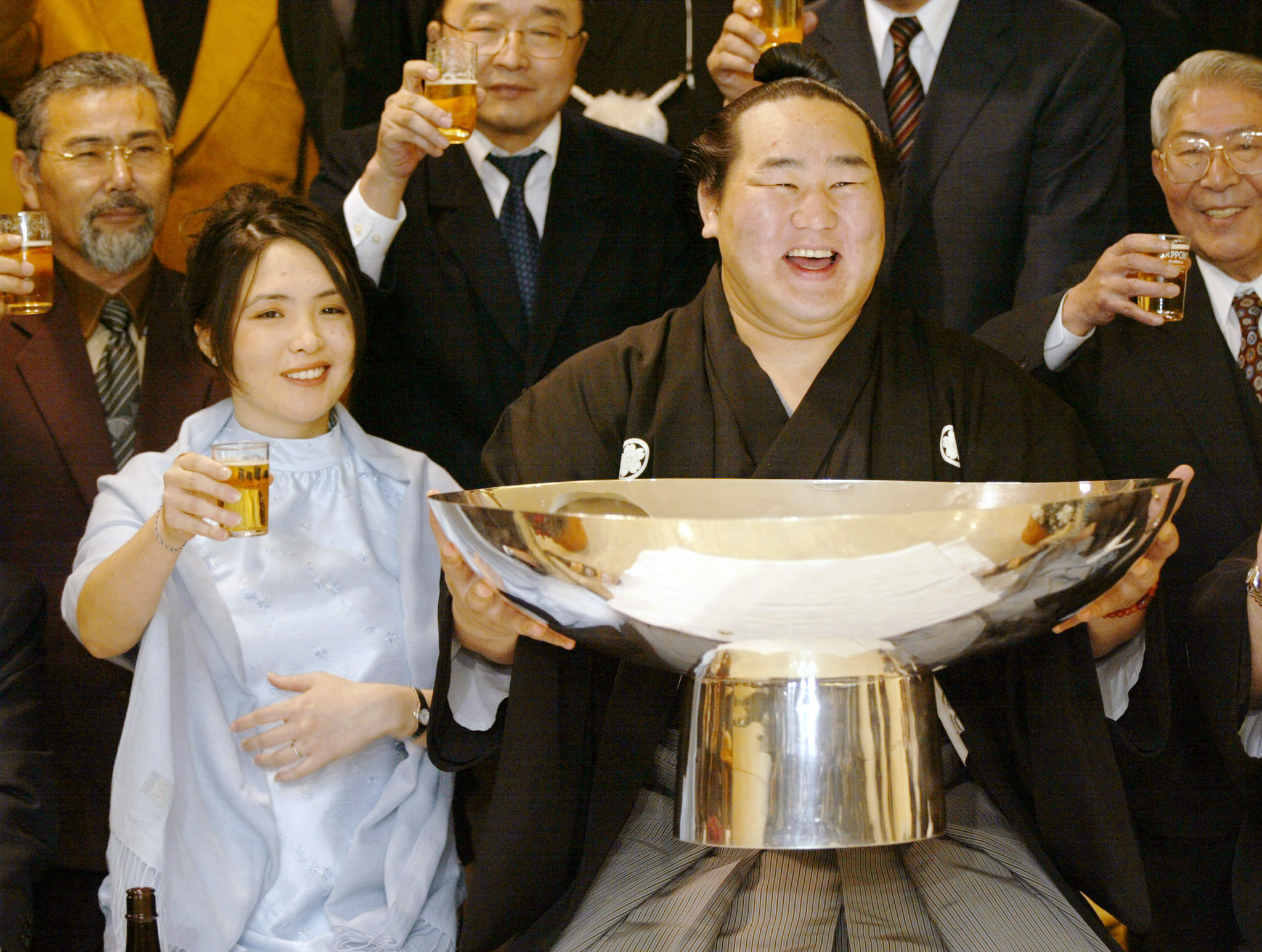 Mongolian sumo wrestler Asashoryu (R) holds a giant traditional Japanese cup containing sake as he is accompanied by his wife Gombotseren Tamir in a toast during a victory celebration in Tokyo January 26, 2003.