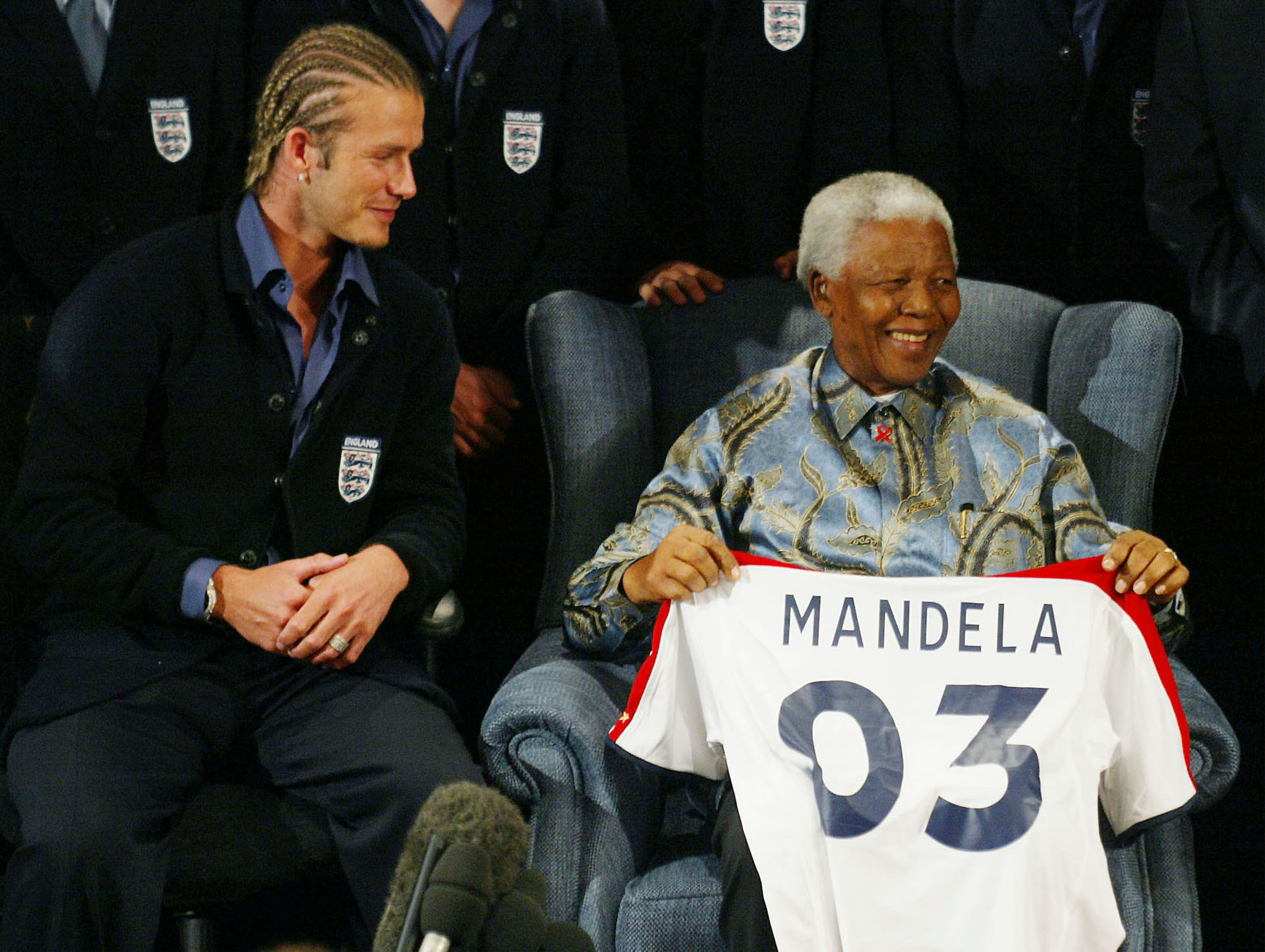 Former South African President Nelson Mandela smiles as he holds up an England soccer shirt he was presented with by England soccer captain David Beckham on behalf of the team, during a meeting at Nelson Mandelas' Foundations office in Johannesburg May 21,2003.