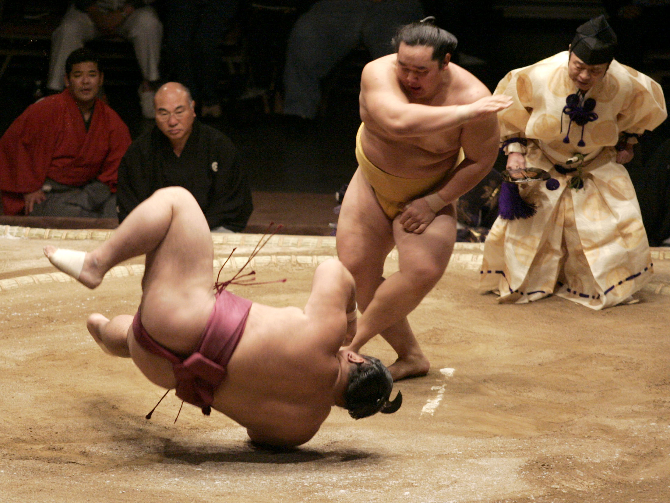 Mongolian sumo wrestler Asashoryu (R) throws down Chiyotaikai (L) of Japan to win the grand championship during the third day of the Grand Sumo Championship Las Vegas tournament at the Mandalay Bay Events Center in Las Vegas, Nevada, October 9, 2005.