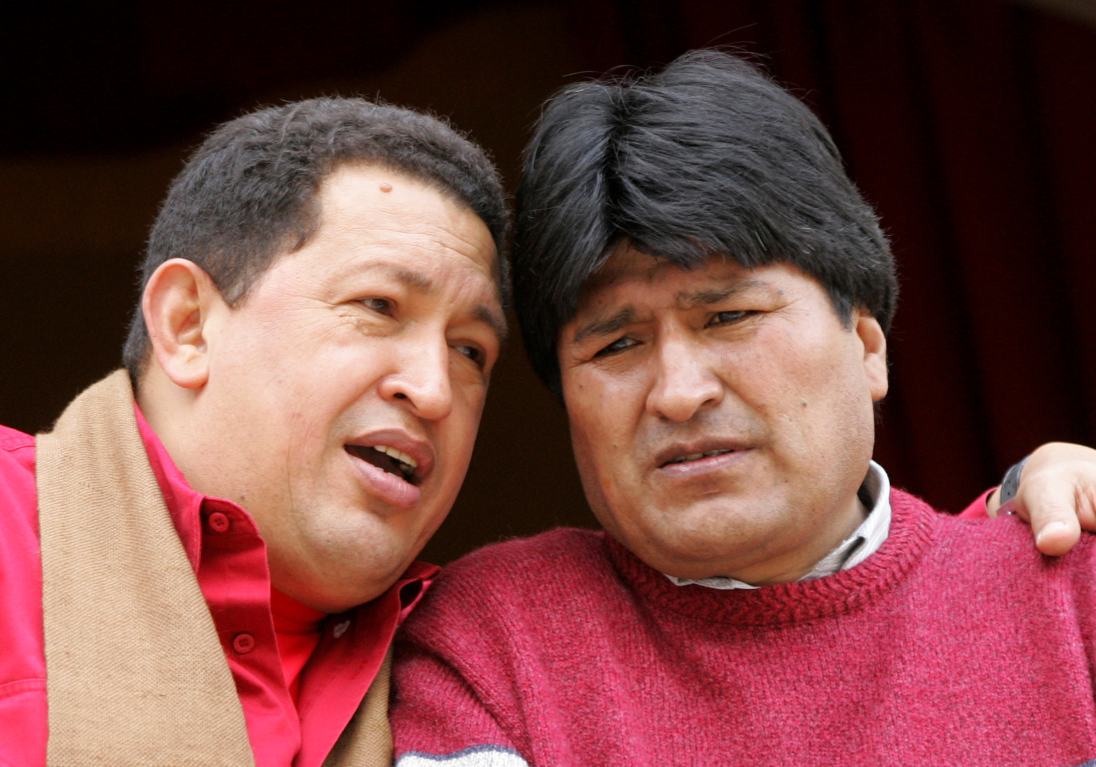 Bolivian President Evo Morales (R) chats with his Venezuelan counterpart Hugo Chavez as they watch a demonstration of folkloric dance from the balcony of the government palace in La Paz January 23, 2006. ©REUTERS/Jose Miguel Gomez