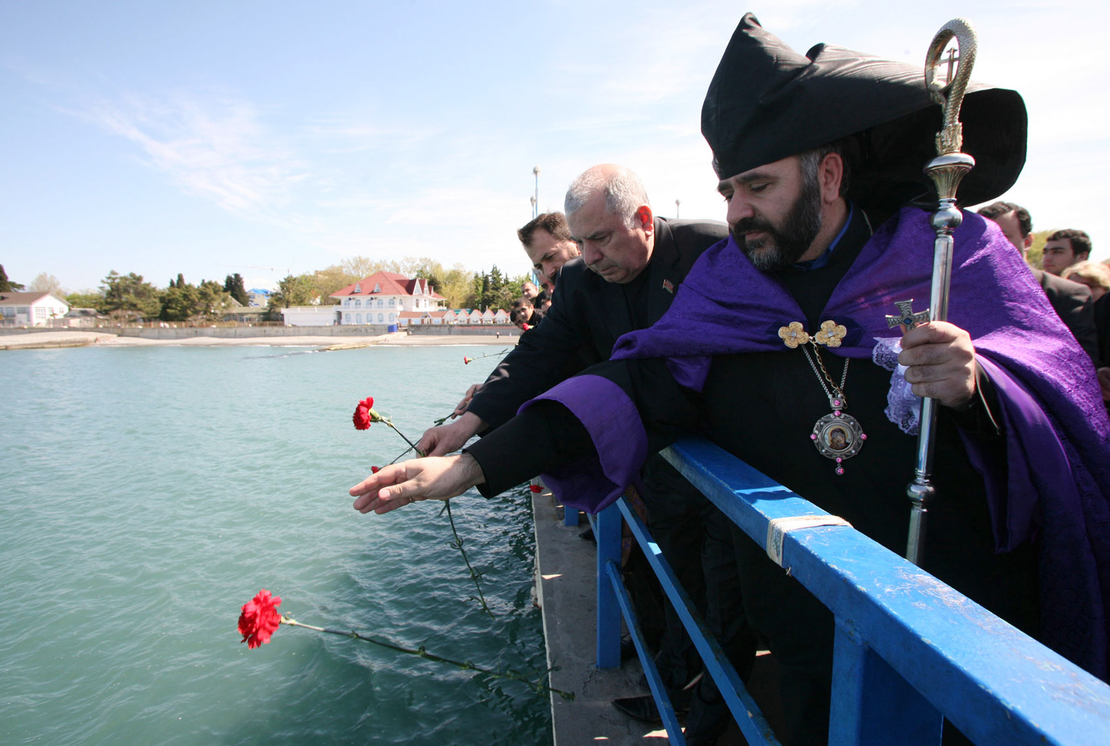 An Armenian priest throws flowers into the sea during a mourning ceremony for victims of the Airbus 320 plane crash in Adler near Sochi. ©REUTERS/Eduard Korniyenko