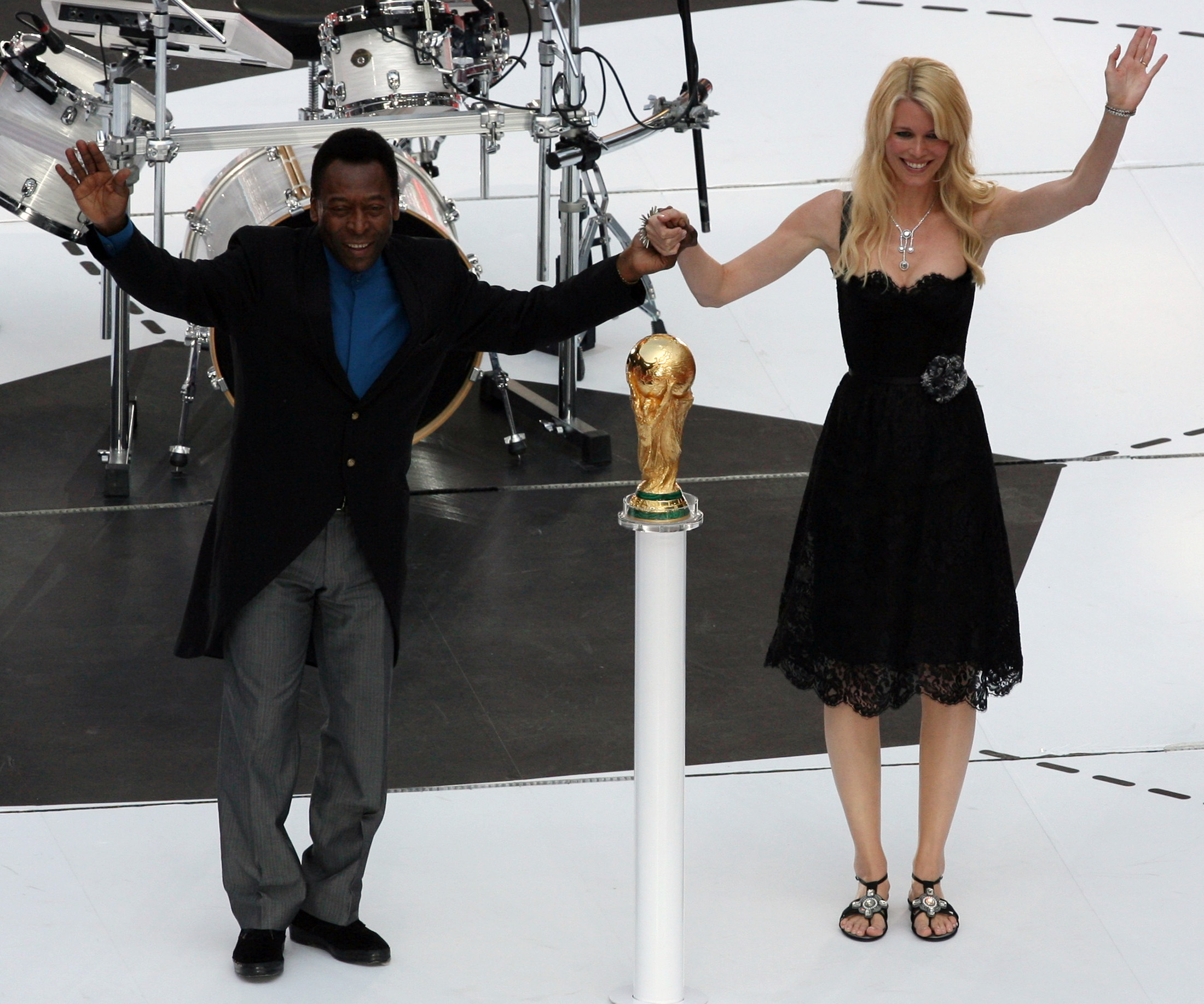 Brazilian soccer legend and member of the 1958, 1962 and 1970 World Cup-winning Brazilian soccer teams Pele holds the hand of German model Claudia Schiffer while standing behind the World Cup Trophy during the World Cup 2006 opening ceremony