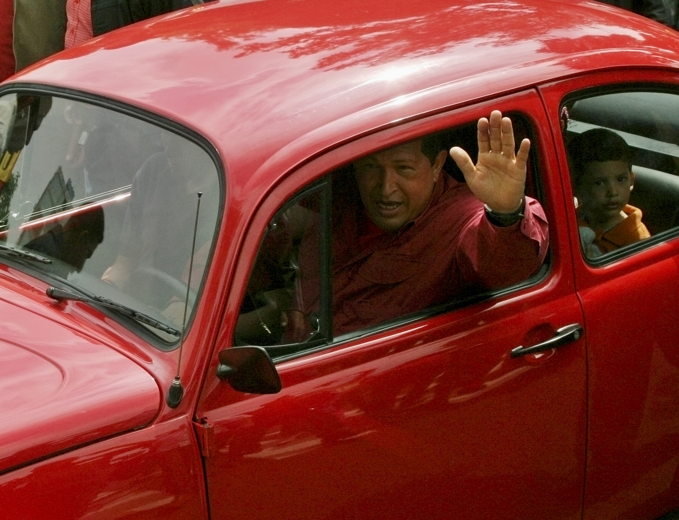 Venezuelan President Hugo Chavez drives his grandson Manuel away in a Volkswagen Beetle after voting in the presidential election at a school in Caracas December 3, 2006. ©REUTERS/Edwin Montilva