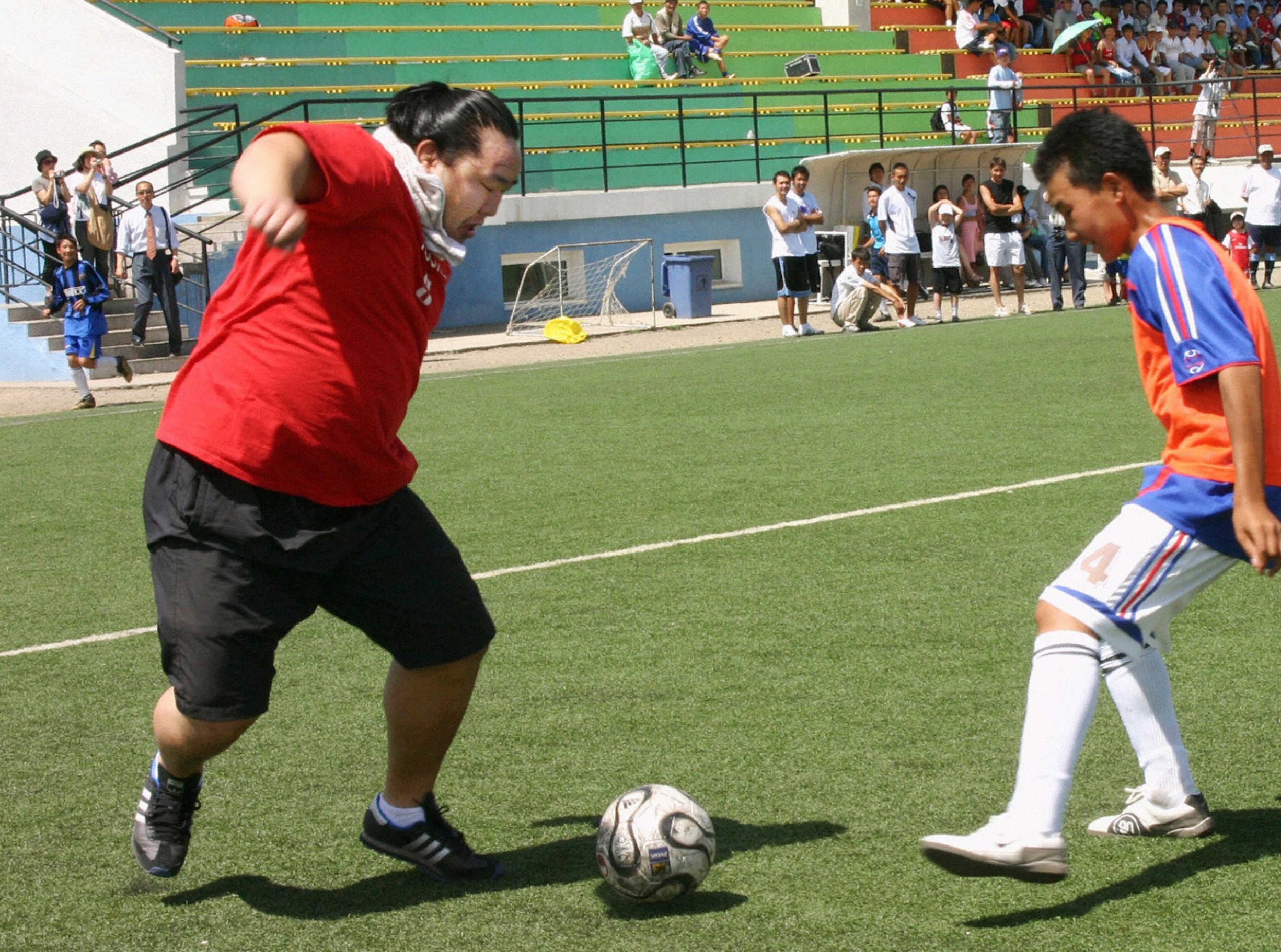 Sumo grand champion Asashoryu (L) plays soccer at a charity match in Ulan Bator, Mongolia