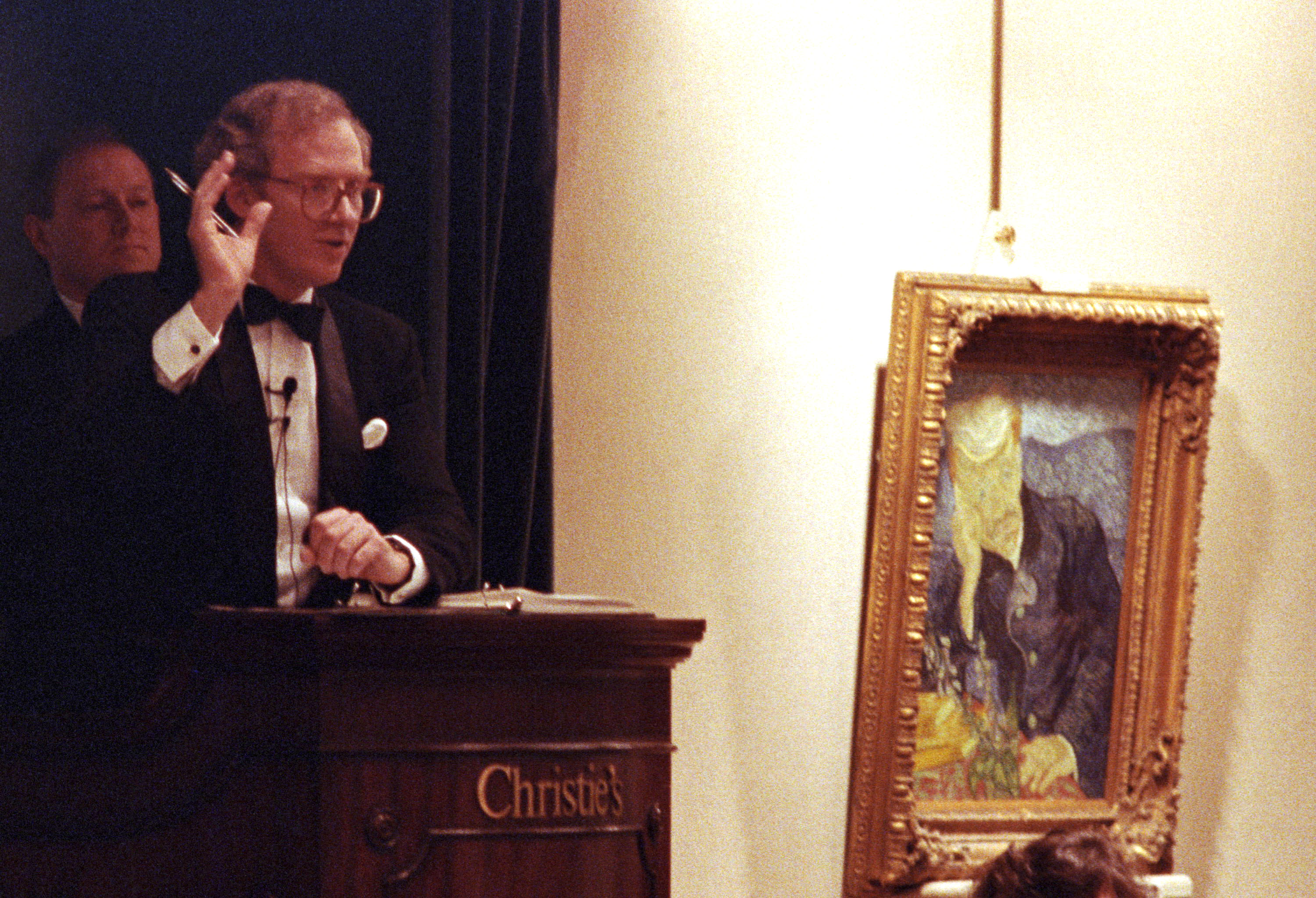 Christopher Burge, President of Christie's in America, (L) hammers down Vincent Van Gogh's