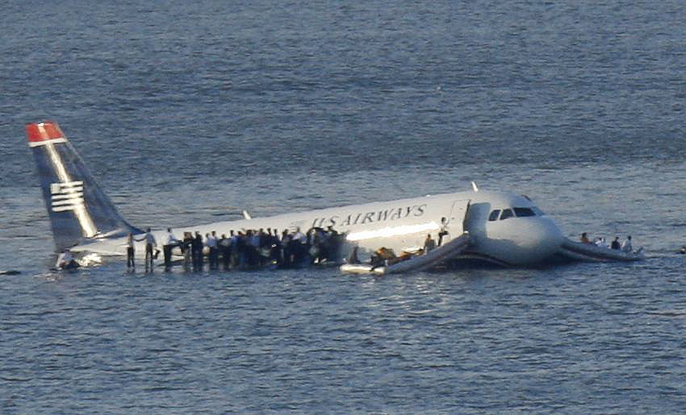 Passengers stand on the wings of a U.S. Airways plane as a ferry pulls up to it after it landed in the Hudson River in New York.