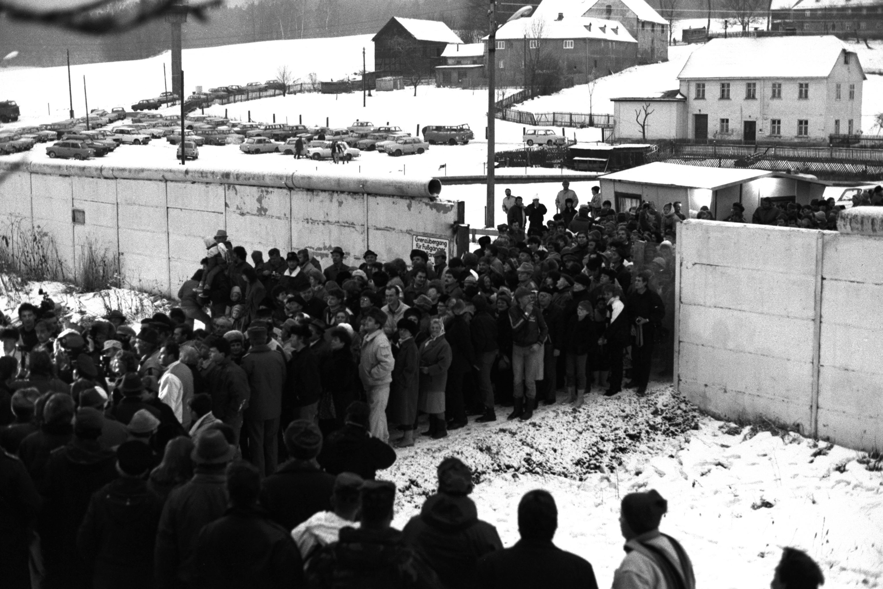 People cross the East German border from East to West Germany, after a border crossing checkpoint was opened at the Wall in the village of Moedlareuth, about 300 kilometres (186 miles) south of Berlin, December 9, 1989. The Wall in the village of Moedlareuth, separating East from West Germany, was built in 1966. It was 700 meters long and 3.40 meters high, heavily guarded round the clock by East German border police and divided the village till the Wall came down in 1989.