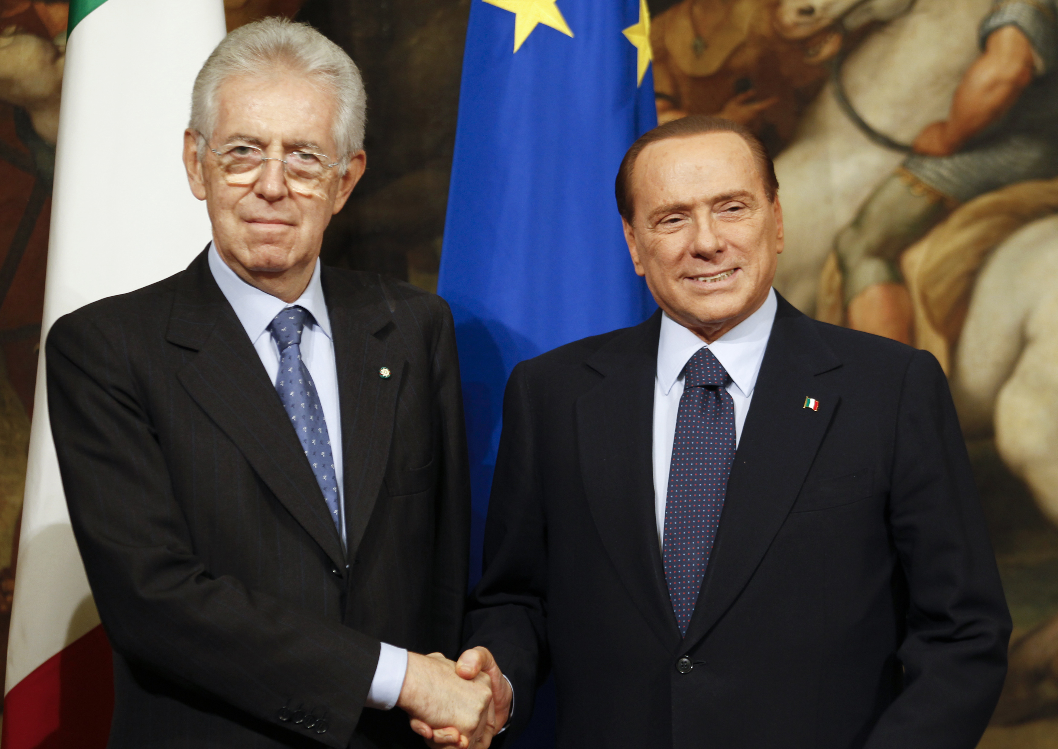 Newly appointed Italian Prime Minister Mario Monti (L) shakes hands with his predecessor Silvio Berlusconi at Chigi Palace in Rome November 16, 2011.