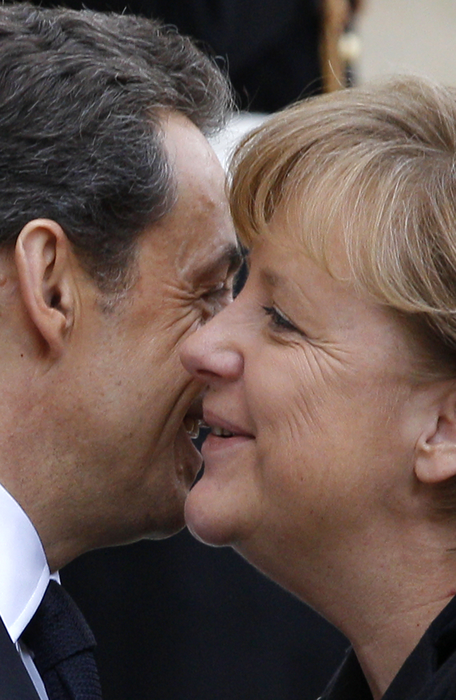 France's President Nicolas Sarkozy (L) embraces German Chancellor Angela Merkel before a working lunch at the Elysee Palace in Paris. ©REUTERS/John Schults