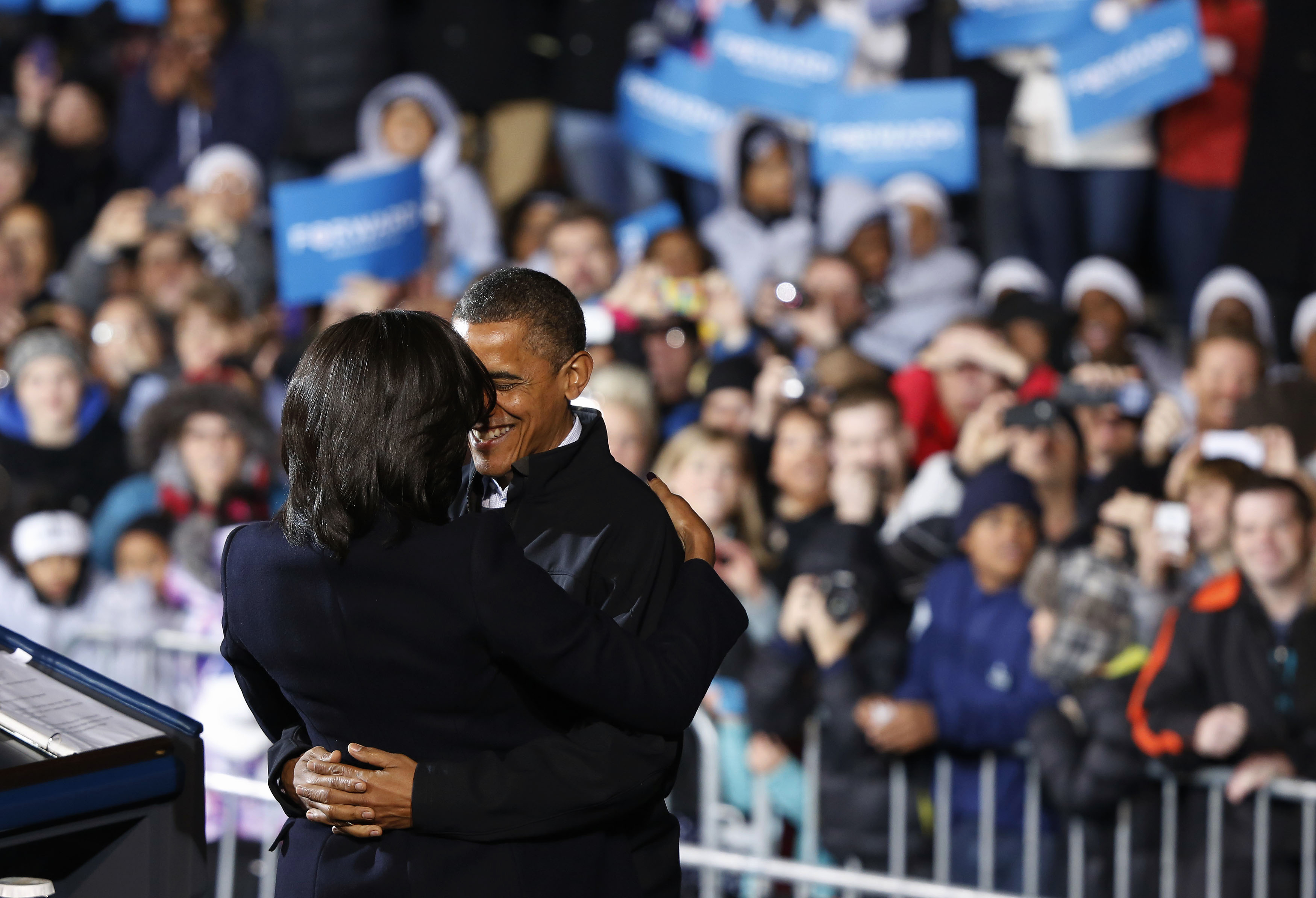 U.S. President Barack Obama hugs First Lady Michelle Obama before he addresses supporters on last night of campaign in a downtown Des Moines, Iowa, rally,