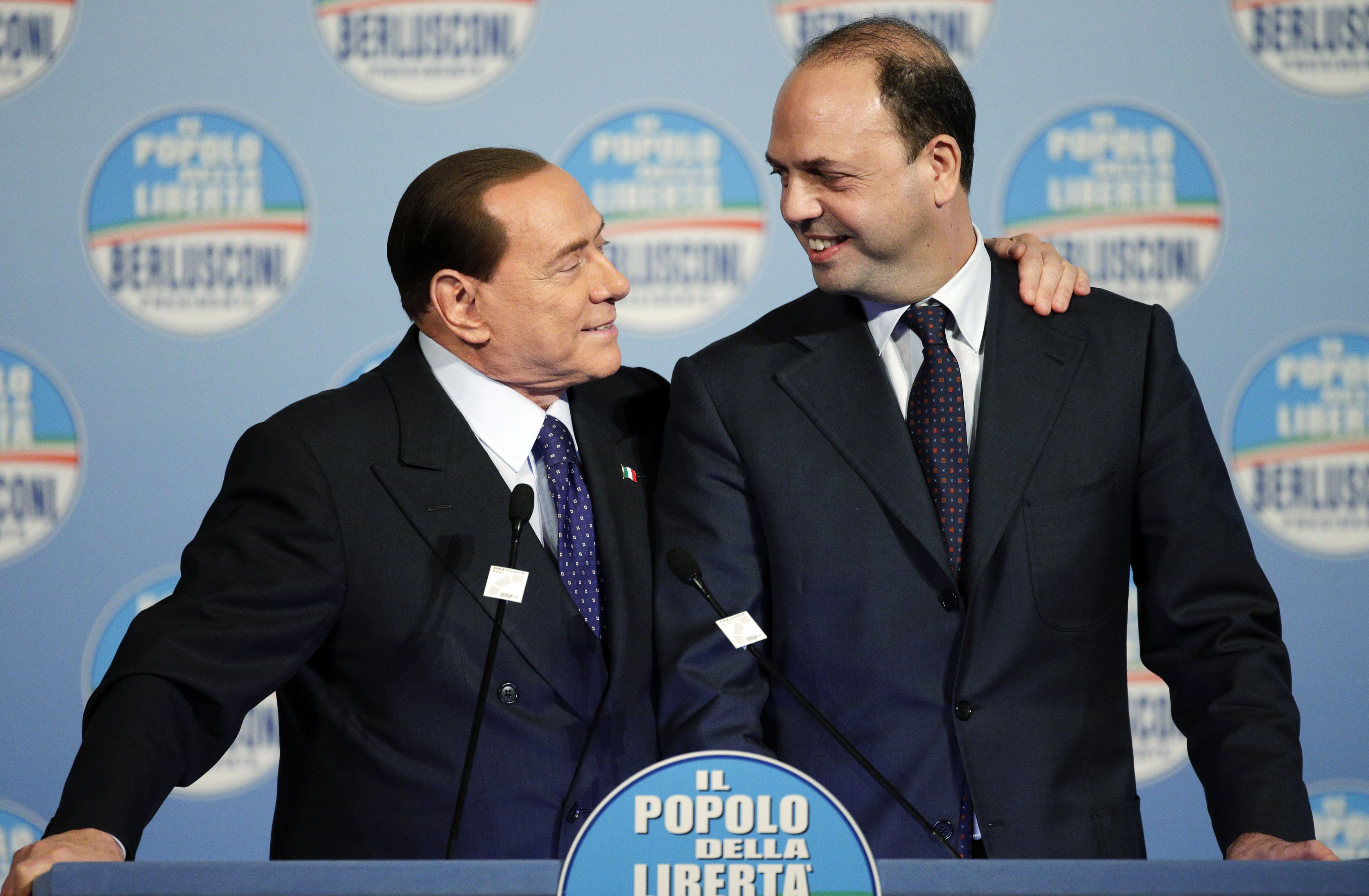 Former Italian Prime Minister Silvio Berlusconi (L) smiles next to People of Freedom Party (PDL) secretary Angelino Alfano as he arrives for a political rally in downtown Rome January 25, 2013.