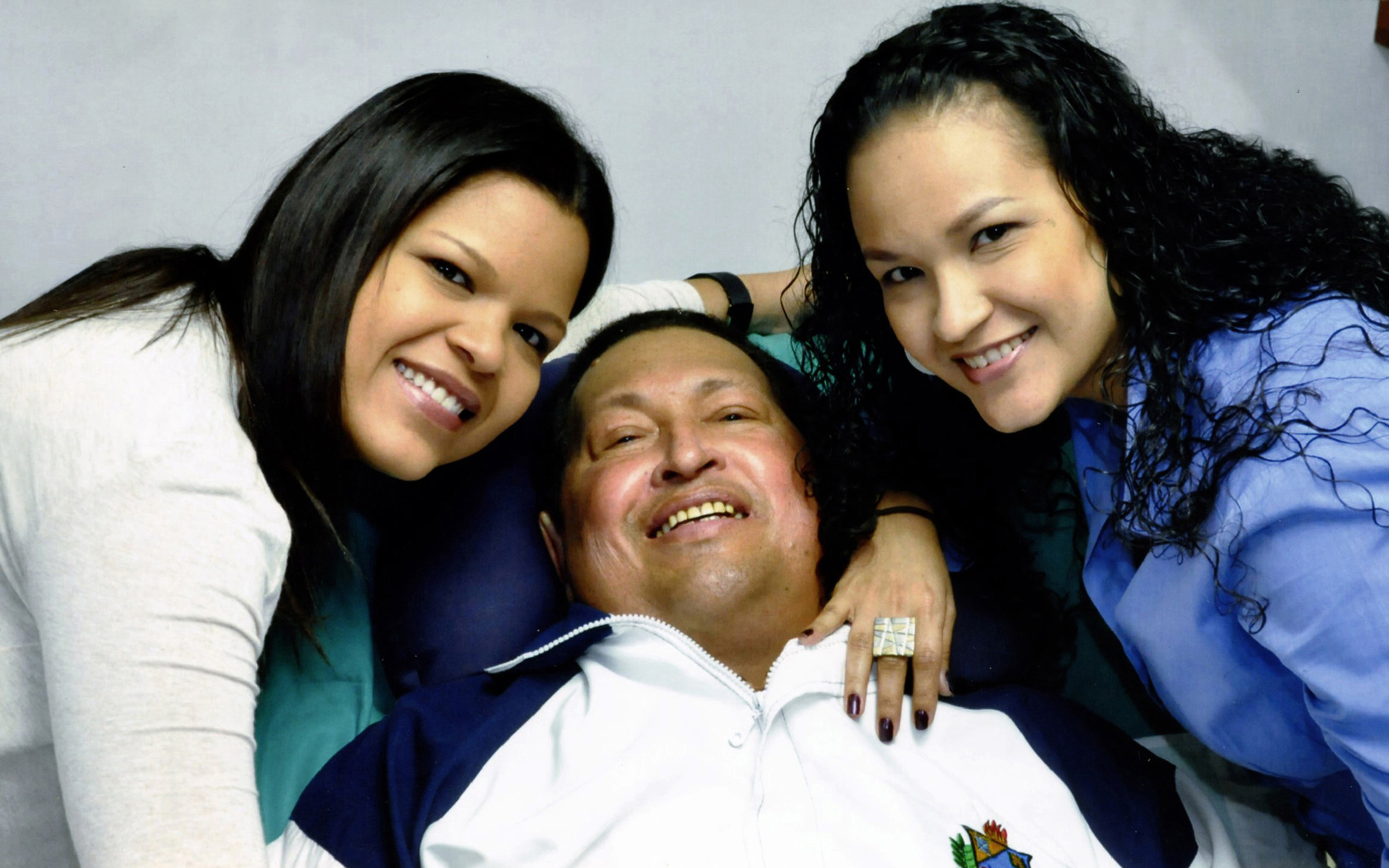 Venezuela's President Hugo Chavez smiles in between his daughters, Rosa Virginia (R) and Maria while recovering from cancer surgery in Havana in this photograph released by the Ministry of Information on February 15, 2013. ©REUTERS/Ministry of Information/Handout