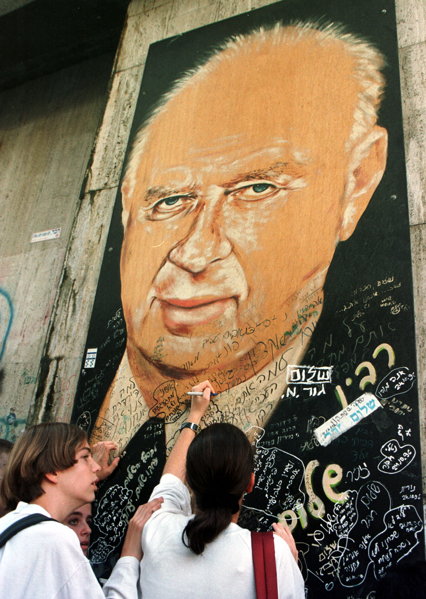 Students write their memorials to Yitzhak Rabin on a portrait of the assassinated Israeli prime minister on November 12, 1995. ©REUTERS/Havakuk Levison