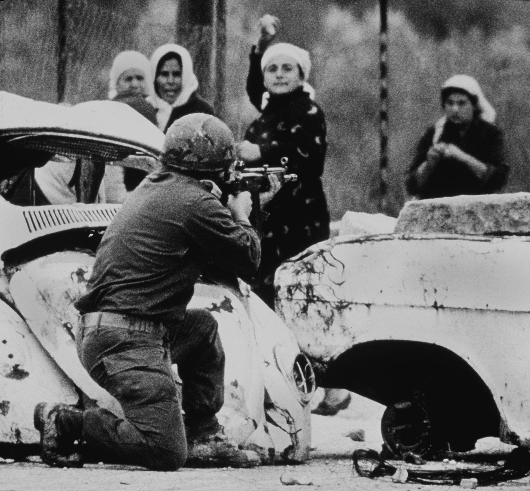 An Israeli soldier takes aim as a Palestinian woman hurls a rock at him from close range during a demonstration on February 29, 1988 in which one Palestinian youth was shot dead several months after the outbreak of the