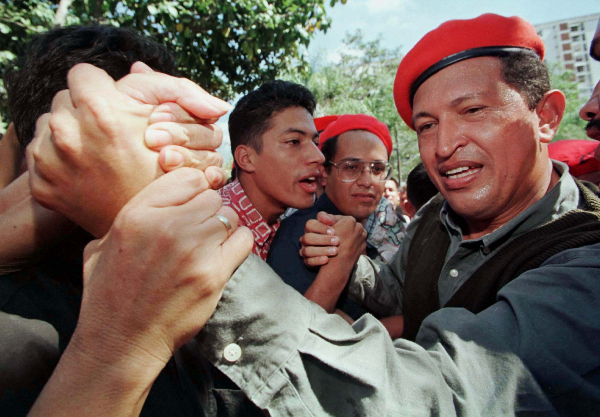 Former Venezuelan coup leader Hugo Chavez Frias shakes hands with a supporter during a political rally in a poor residential area of Caracas January 31, 1998. ©REUTERS