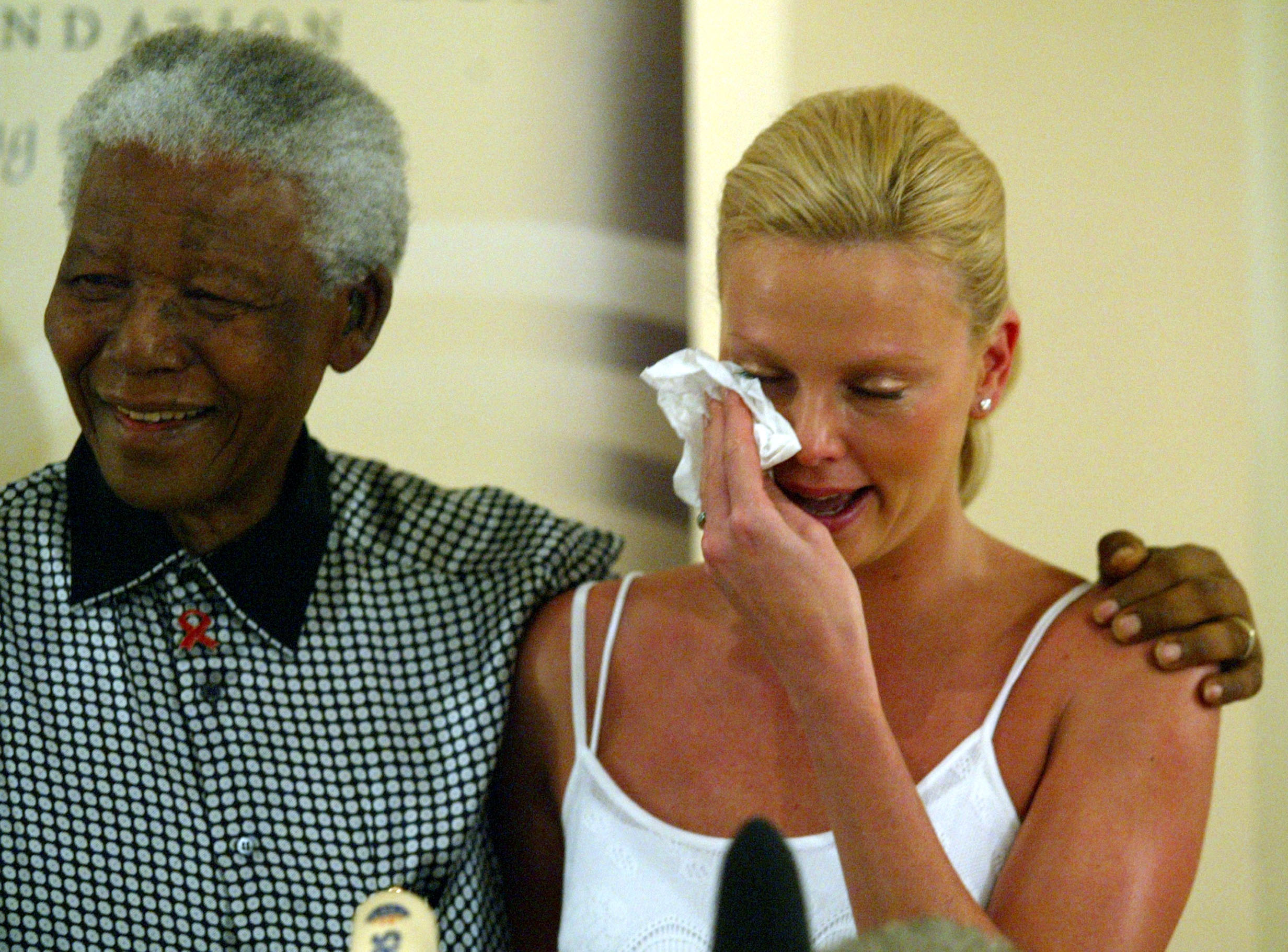 Oscar winning South African actress Charlize Theron weeps at her meeting with former South African President Nelson Mandela (L) at the Nelson Mandela Foundation in Houghton Johannesburg March 11,2004. REUTERS/Juda Ngwenya