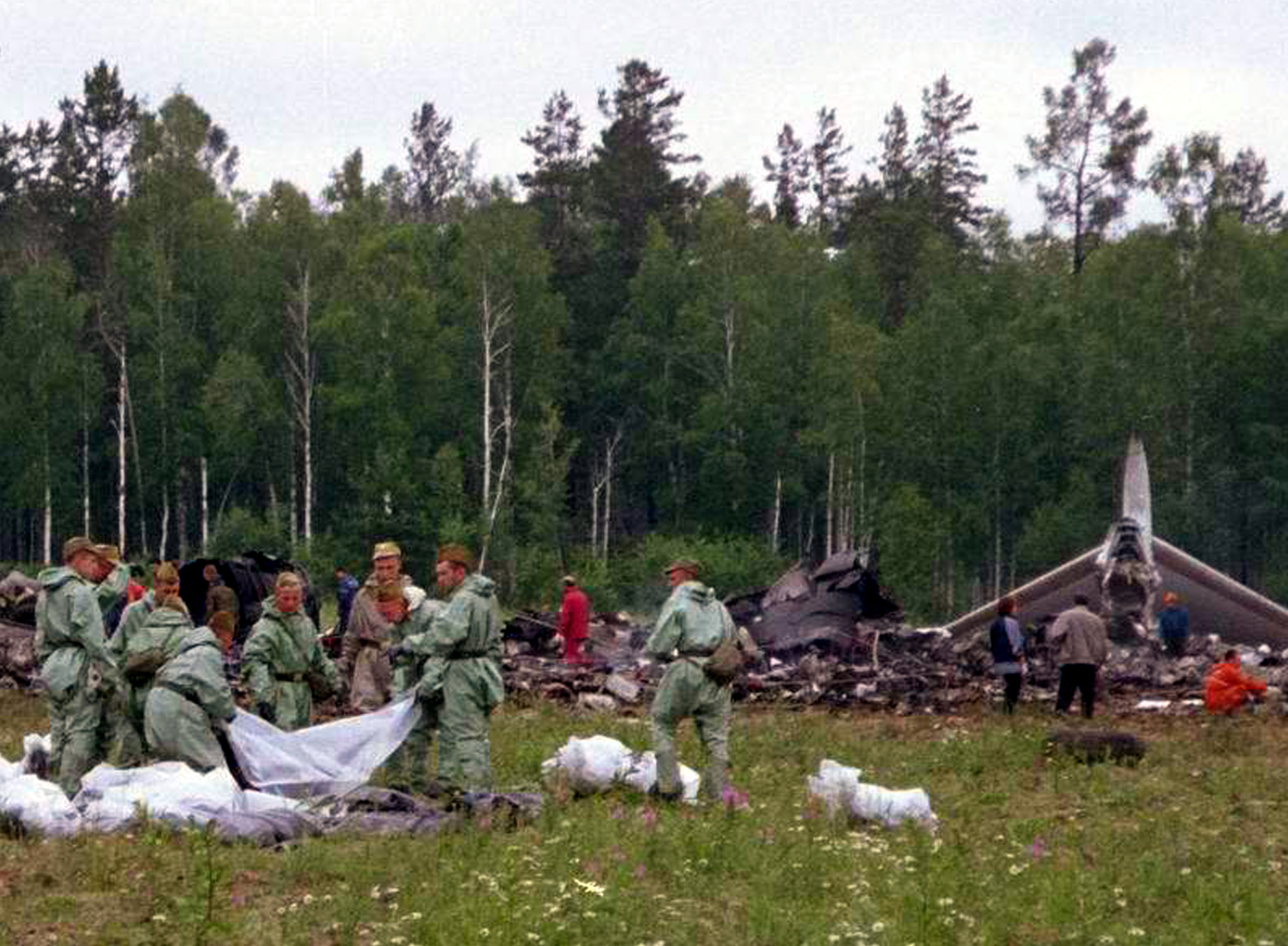 Russian rescue workers collect the remains of people, July 4, 2001, killed in the crash of Tupolev Tu-154 plane 30 kilometers (18 miles) away from Irkutsk. ©REUTERS