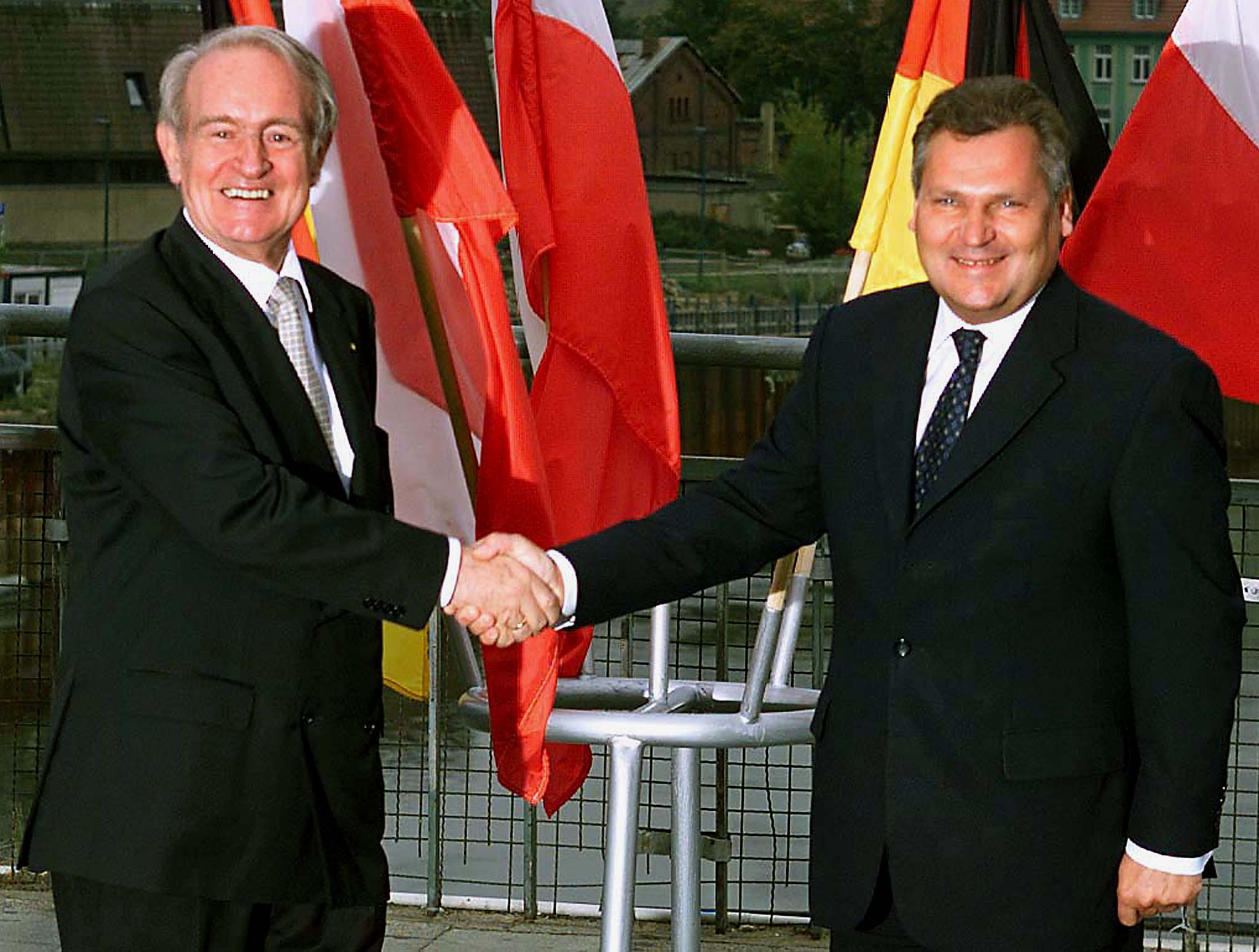 German President Johannes Rau (L) makes a symbolic handshake with Polish President Alexander Kwasniewski as they meet on the German-Polish border on the bridge between Frankfurt Oder and Slubice September 1. Rau and Kwasniewski take part in several ceremonies on Wednesday to mark the 60th anniversary of Nazi Germany's attack on Poland which was the start of World War II.