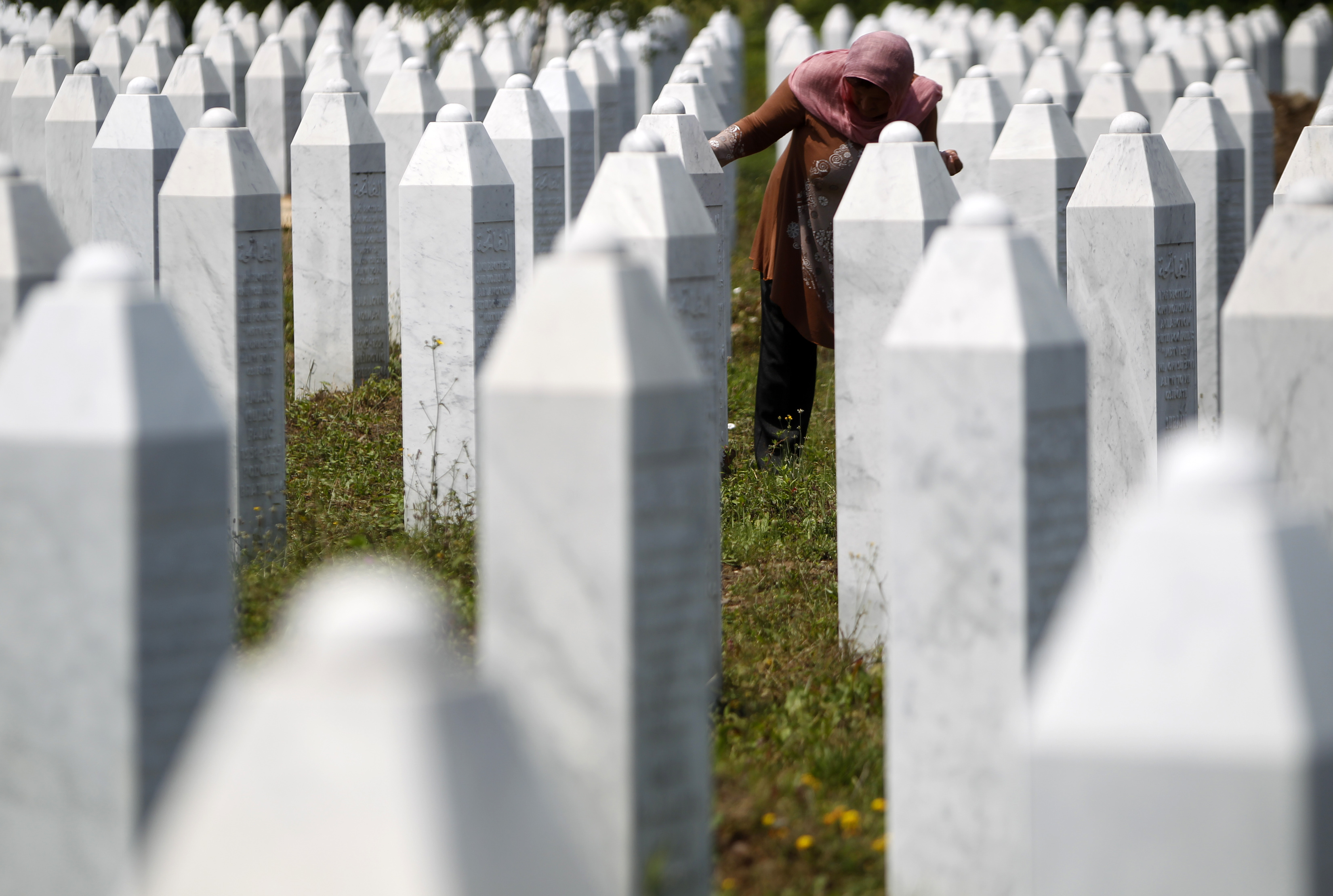 A Bosnian woman tries to find the grave of her relative in Memorial Center Potocari near Srebrenica July 10, 2013. The bodies of the recently identified victims will be transported to the memorial centre in Potocari where they will be buried on July 11 marking the 18th anniversary of the massacre in which Bosnian Serb forces commanded by Ratko Mladic killed up to 8,000 Muslim men and boys and buried them in mass graves. REUTERS/Dado Ruvic