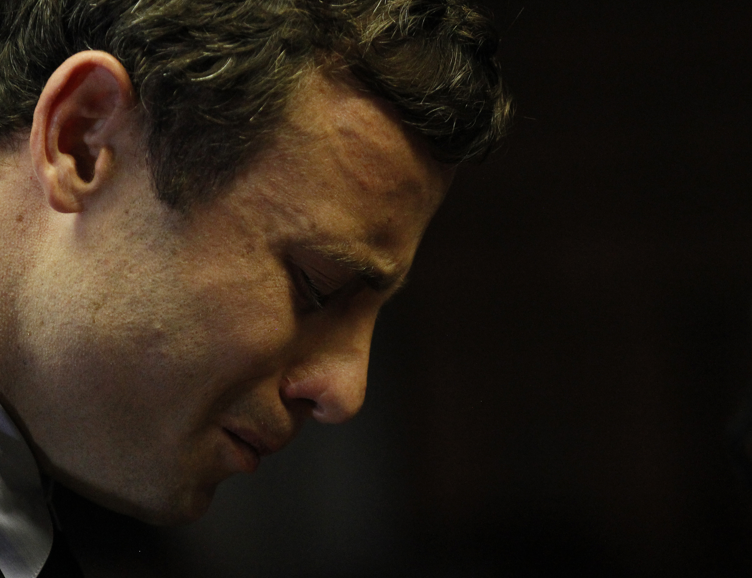 Olympic and Paralympic running star Oscar Pistorius reacts ahead of court proceedings at the Pretoria Magistrates court, August 19, 2013. Pistorius, accused of murdering his model girlfriend, prayed and wiped away tears in a court hearing on Monday which set a March 3, 2014 start date for his trial. REUTERS/Siphiwe Sibeko
