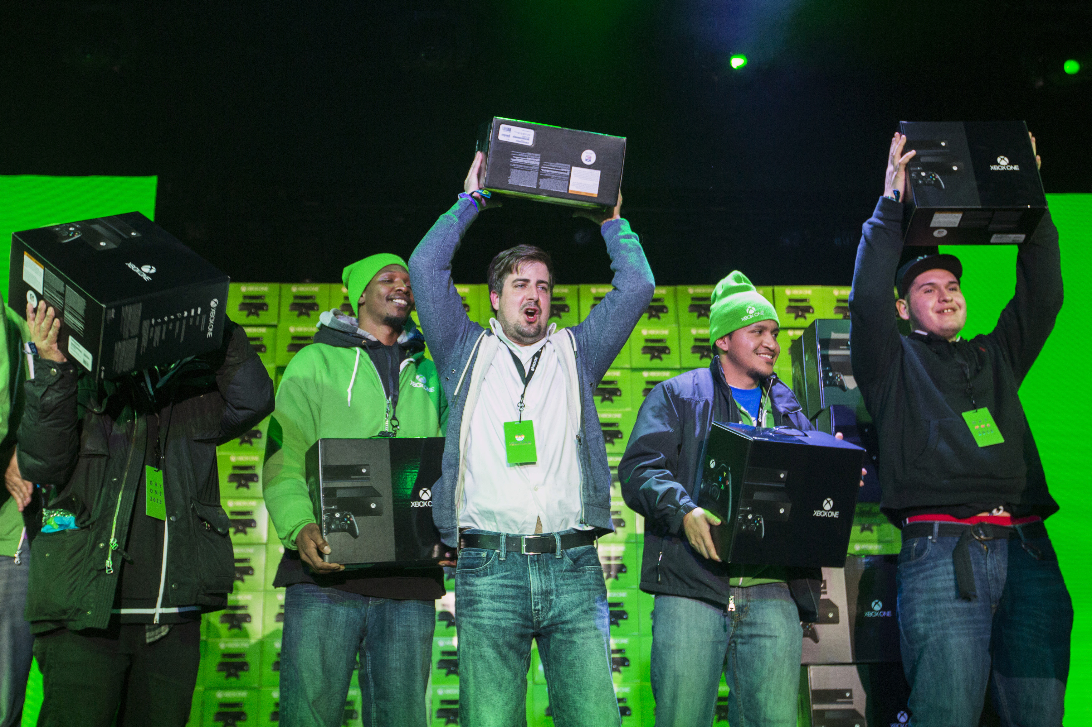 Customers hold aloft their Xbox One consoles purchased during a midnight launch event in New York November 22, 2013. REUTERS/Lucas Jackson