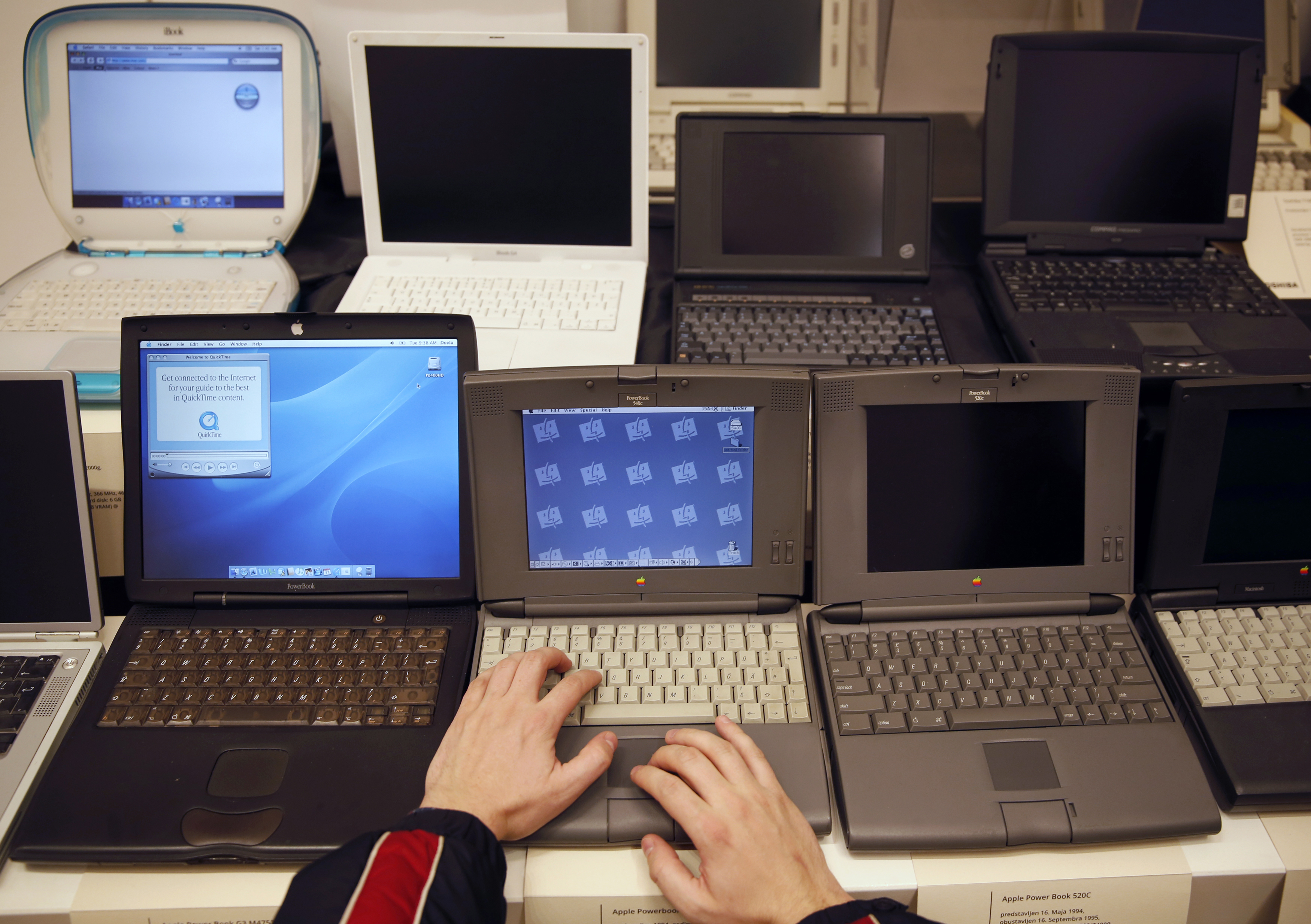 A man works on an Apple PowerBook 540c laptop during the
