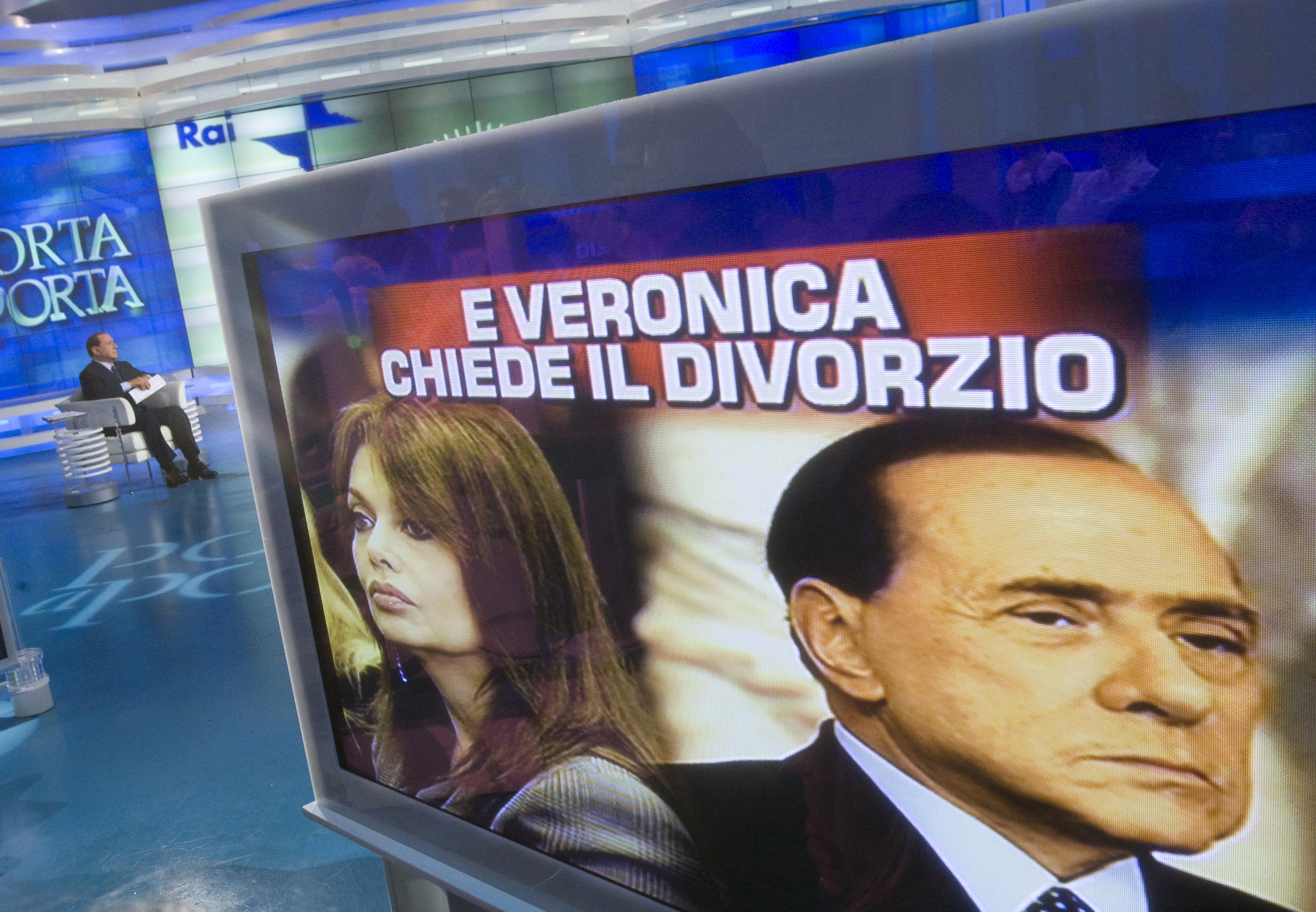 Italy's Prime Minister Silvio Berlusconi (L) sits near a television monitor showing images of him and his wife Veronica Lario during the taping of the television program Porta a Porta (