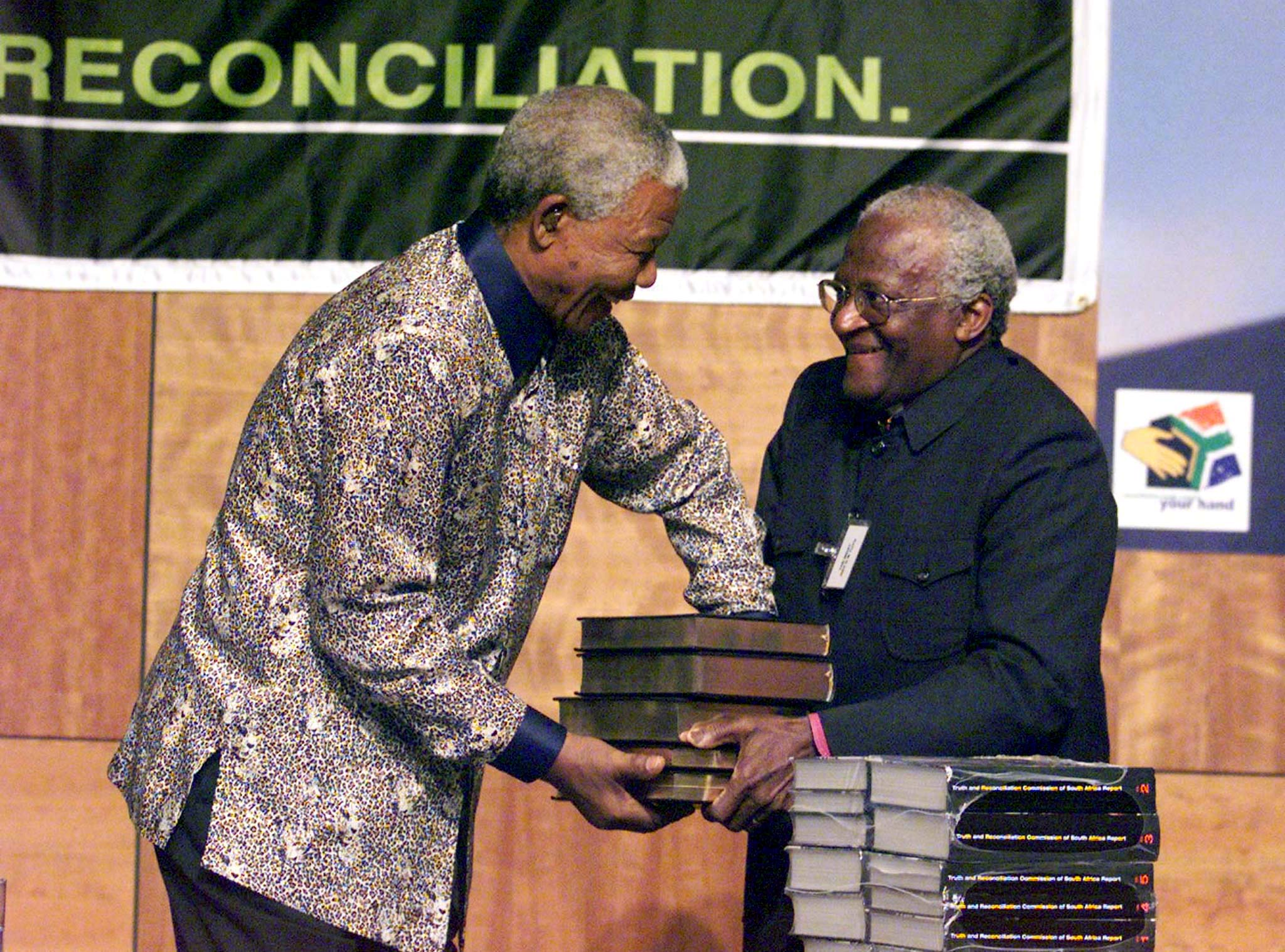Chairman of the TRC (Truth and Reconciliation Commission) Archbishop Desmond Tutu (R) hands over the TRC report to South Africa's President Nelson Mandela at the State theater Building in Pretoria October 29.