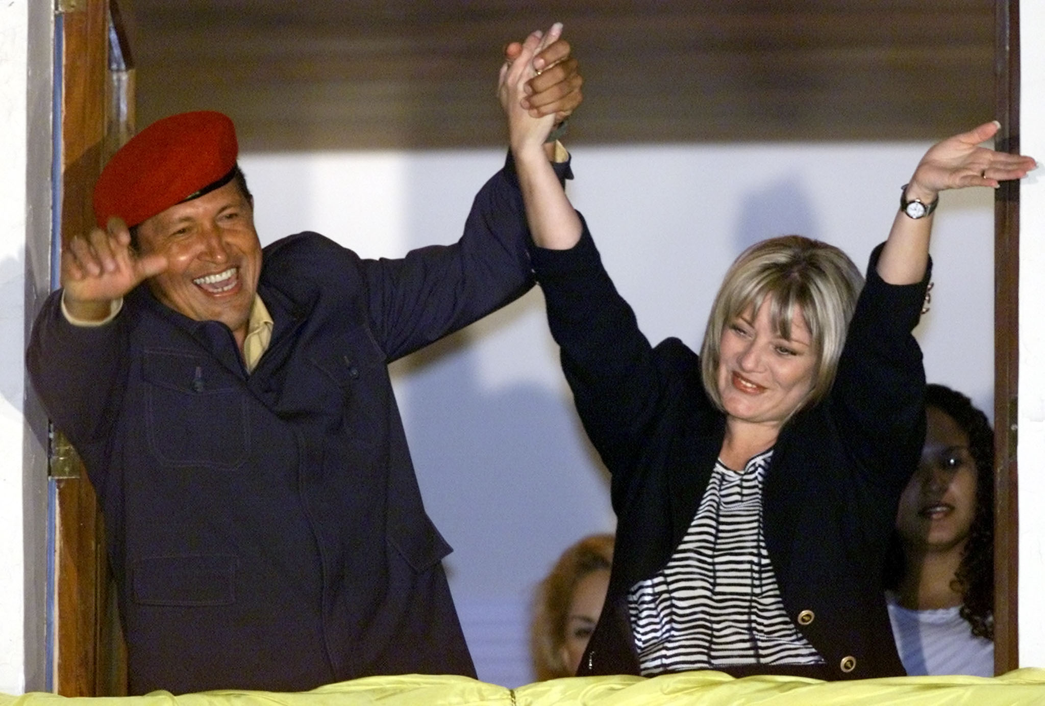 Venezuelan President Hugo Chavez (L) and his wife Marisabel wave to supporters from the balcony of the presidential palace while celebrating the first official results that showed Chavez with a clear victory over rival [Francisco Arias] in general elections held July 30, 2000. ©REUTERS