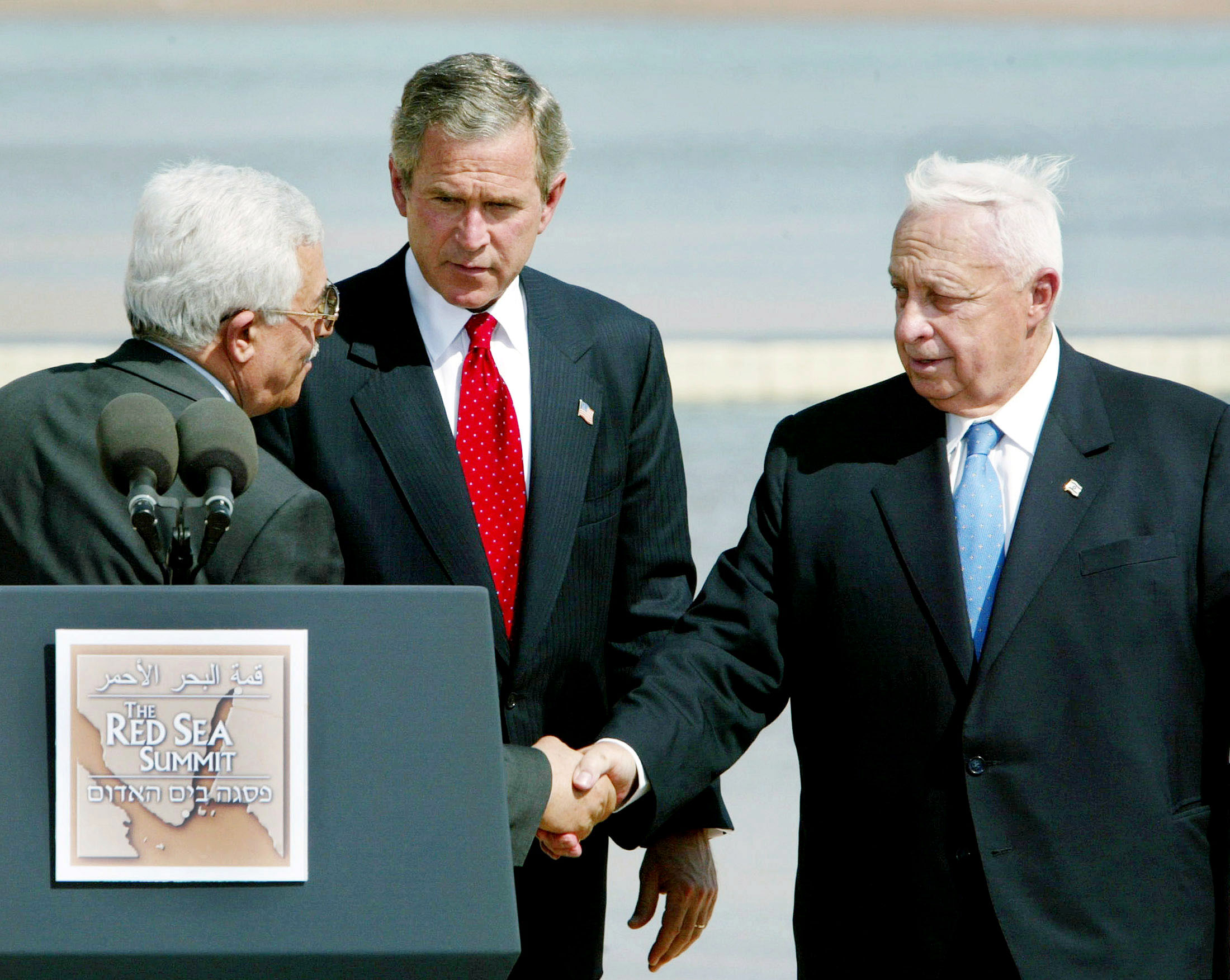 U.S. President George W. Bush (C) watches as Israel Prime Minister Ariel Sharon (R) and Palestinian Authority Prime Minister Mahmoud Abbas (L) shake hands. ©REUTERS/Larry Downing