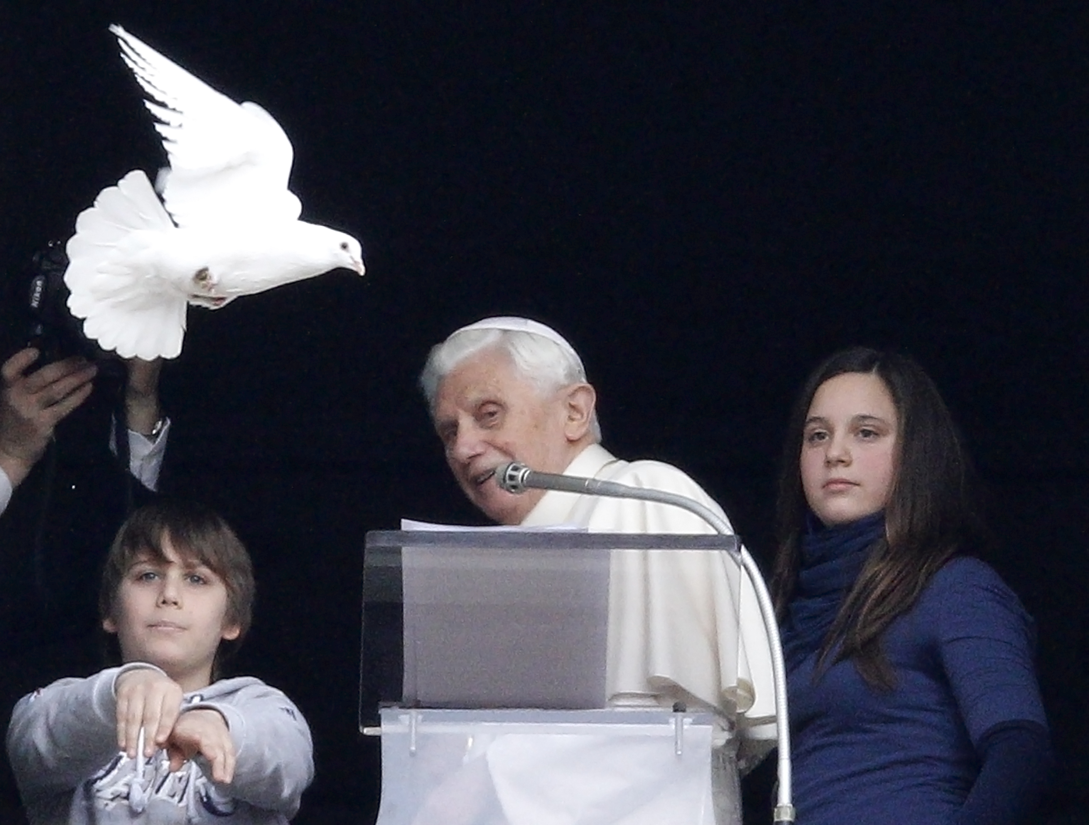 Pope Benedict XVI reacts next two young members of