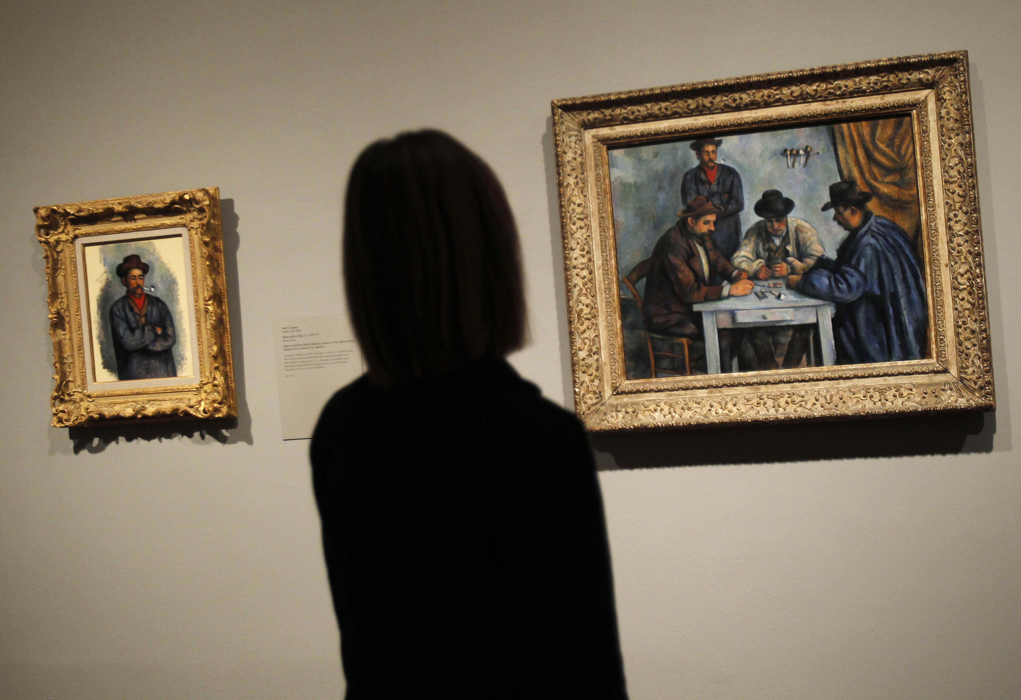 A woman views oil on canvas paintings (L-R) by artist Paul Cezanne titled 'Man with a Pipe' (1890-92) and 'The Card Players' (1890-92) are seen during a press preview for Cezanne's Card Players exhibit at The Metropolitan Museum of Art in New York