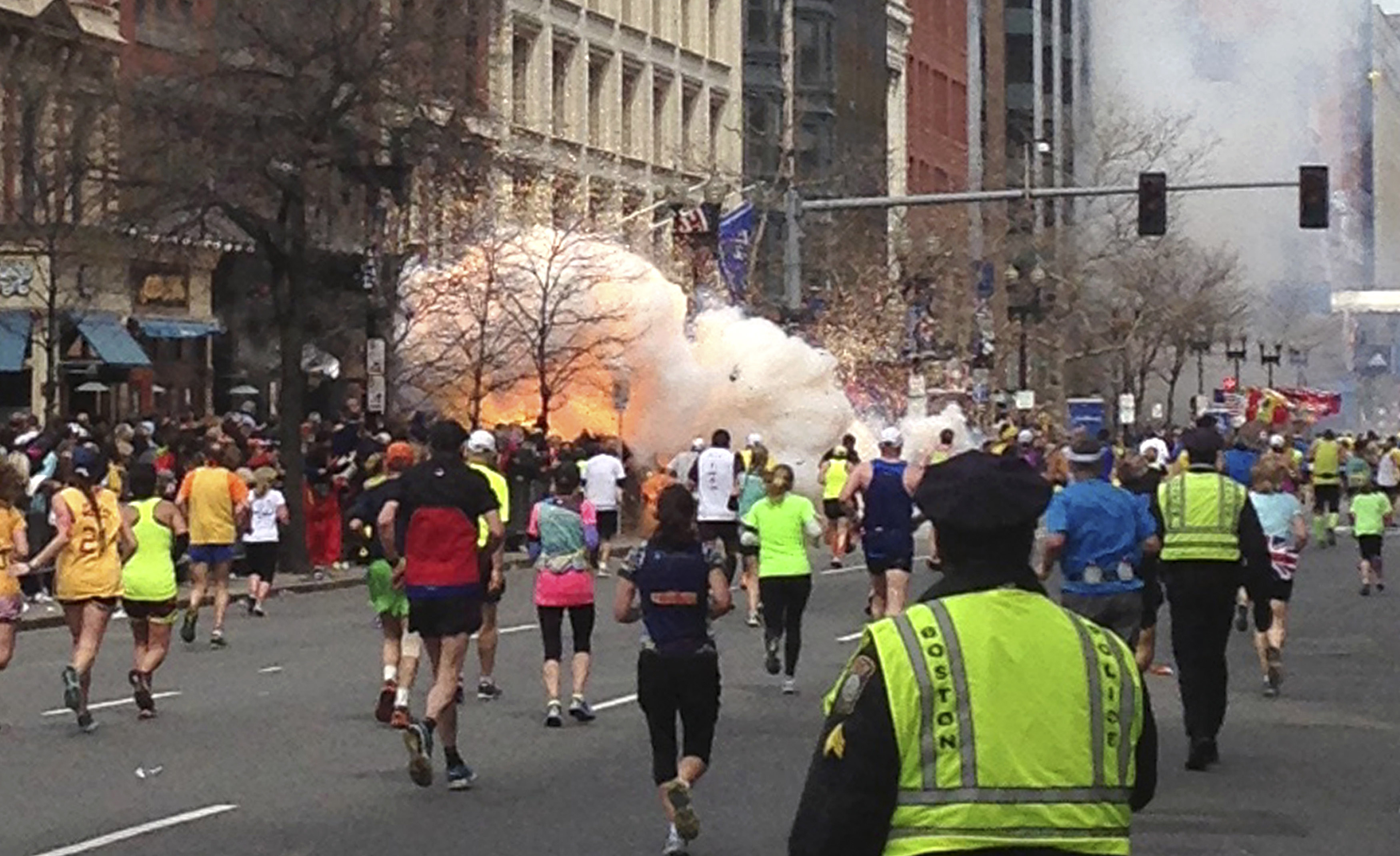 Runners continue to run towards the finish line of the Boston Marathon as an explosion erupts near the finish line of the race in this photo exclusively licensed to Reuters by photographer Dan Lampariello after he took the photo in Boston, Massachusetts, April 15, 2013.