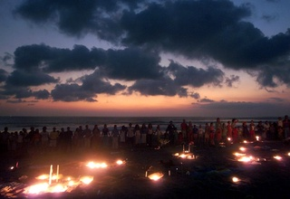Westerners and Balinese join hands during a candlelight vigil for bomb victims at dusk October 14, 2002, on a beach near Kuta on the Indonesian resort island of Bali. ©Reuters