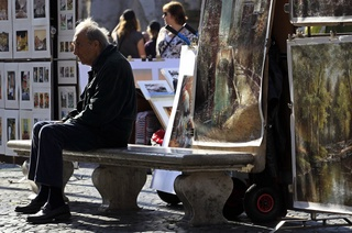 A man sits on a bench at Navona Square in Rome November 10, 2011. ©REUTERS/Stefano Rellandini