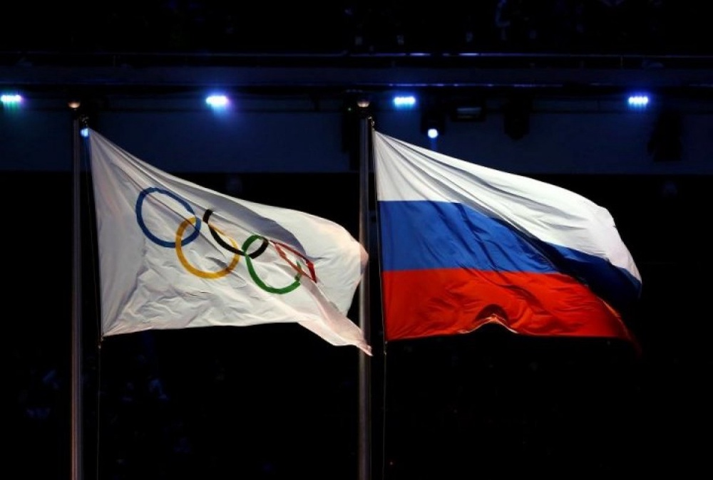 The Olympic flag (L) and the Russian flag are hoisted during the Opening Ceremony of the Sochi Winter Olympics. ©sochi2014.com