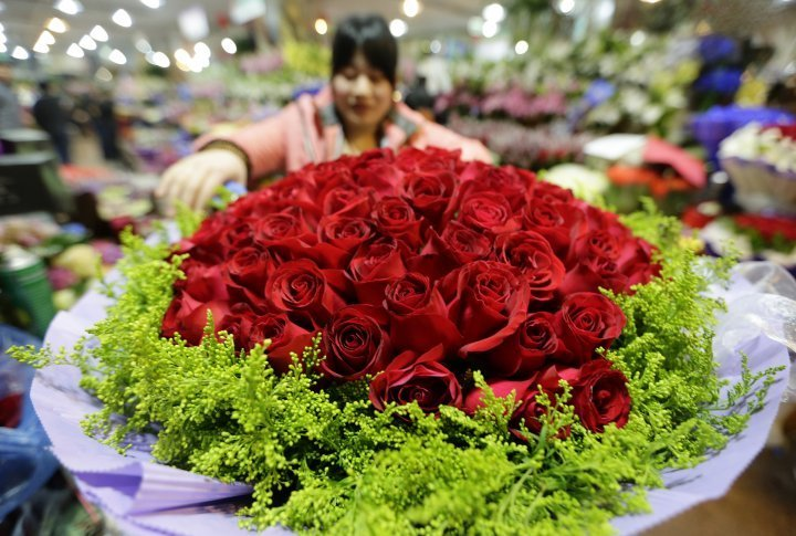 A florist decorating a bouquet of 99 red roses in Beijine, China. ©Reuters