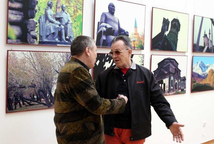 Actor Gennadiy Balayev talks to one of the visitors of the exhibition.