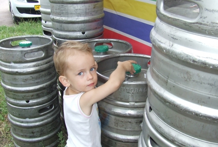 A kid trying to find beer in barrels. ©Roza Yessenkulova