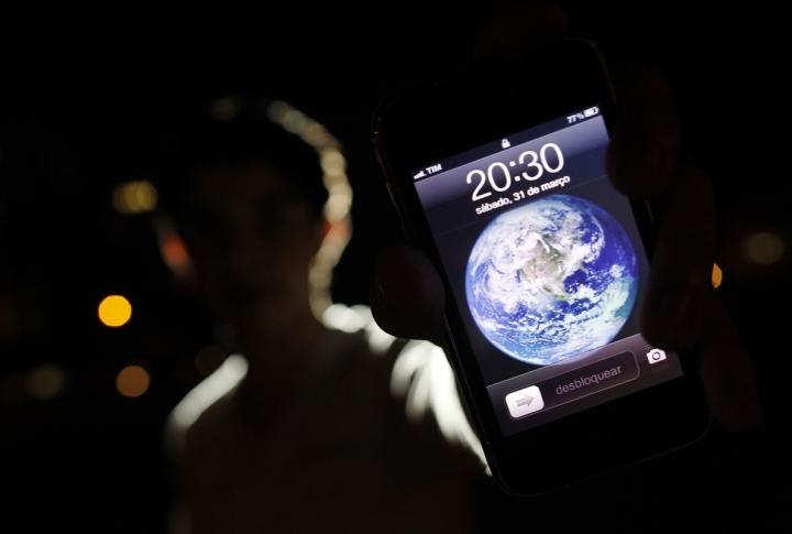 A man poses with an iPhone during Earth Hour in the center of Brasilia, Brazil. ©REUTERS/Ueslei Marcelino