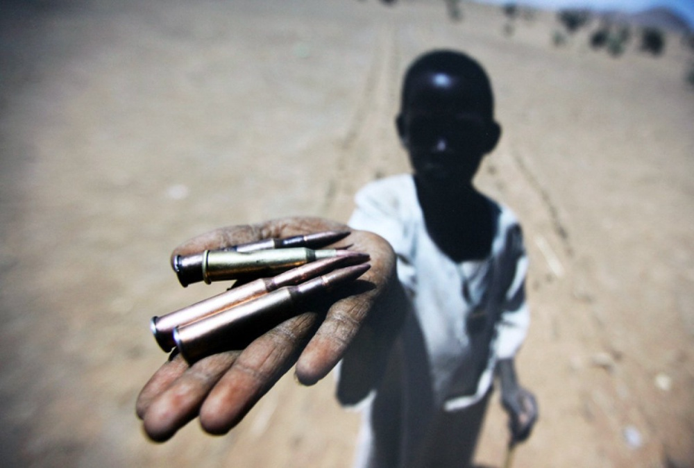 A kid holding bullets collected from the ground in Northern Darfur's village. March 27, 2011<br> UN Photo/Albert Gonzalez Farran©
