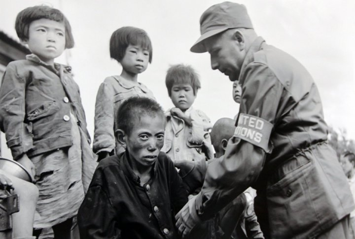 Orphans found wondering in the ruins of Seoul are taken to an orphanage by UN officer. <br>UN Photo/GM©