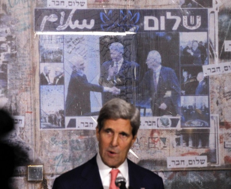U.S. Secretary of State John Kerry is pictured in front of a photo showing U.S. President Bill Clinon, Jordan's King Hussein and Yitzhak Rabin, as Kerry marks the 18th anniversary of Rabin's assassin