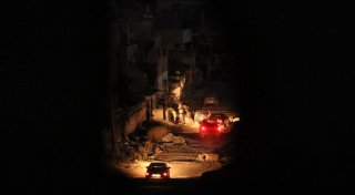 A picture taken through a hole in a wall shows cars driving at night past damaged buildings in the city of Benghazi following fierce fighting with armed groups including Islamic State (IS) jihadists.