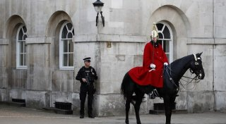 An armed British police officer (L) holds his automatic weapon as he stands on duty whilst a member of the The Life Guards sits on his horse during the Changing the Guard ceremony on Horseguards Parad