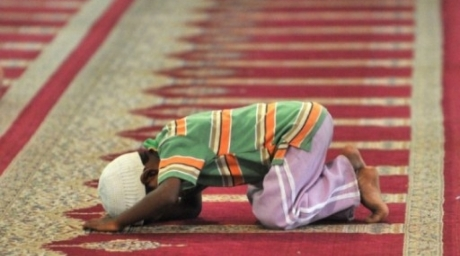 A Muslim child offers prayers at the Jama Masjid mosque, India. ©AFP